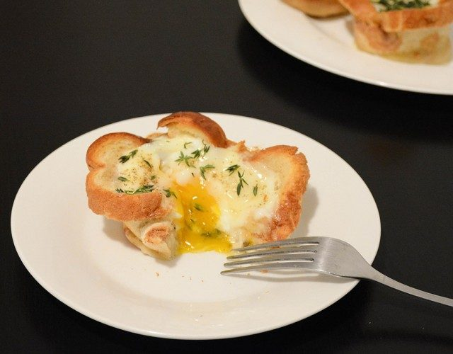 croque madame egg cup ona plate after being cut open with a fork