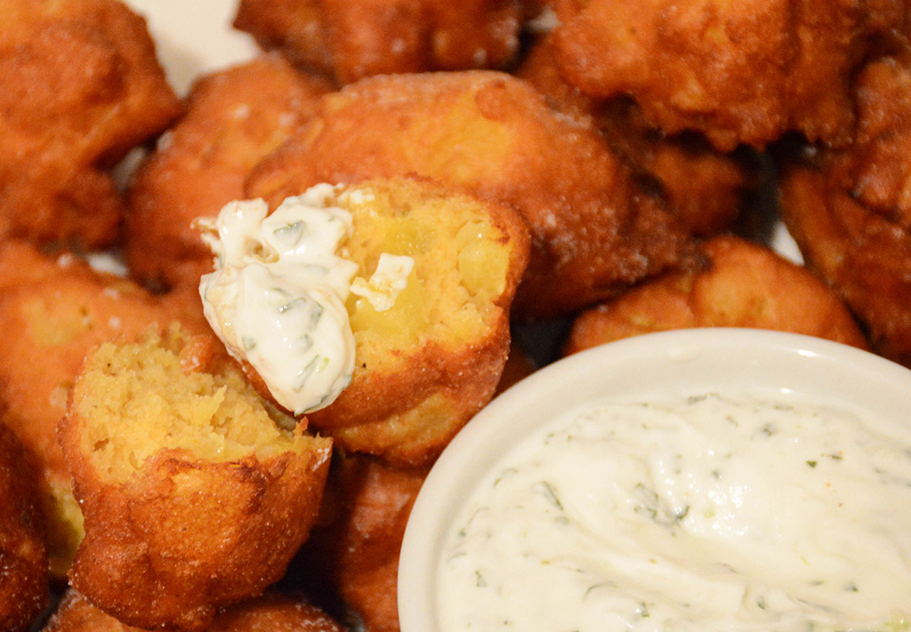close-up of a curried pineapple fritter dunked in mint-lime yogurt