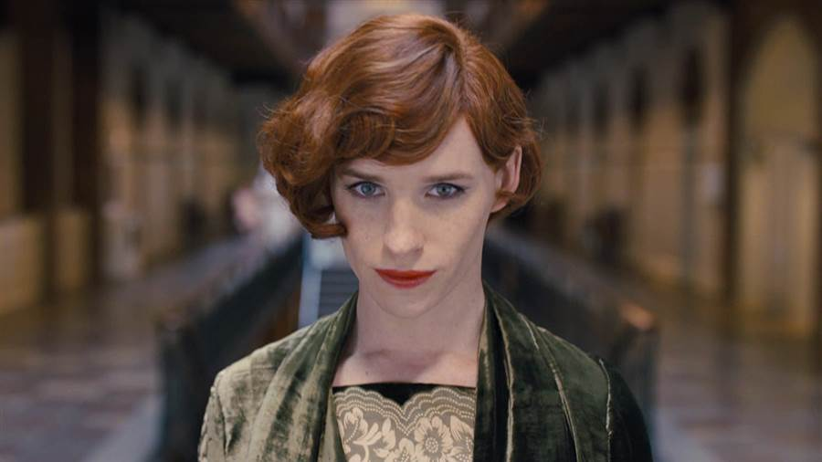 Eddie Redmayne dressed as a woman, wearing a green dress, and donning red lipstick