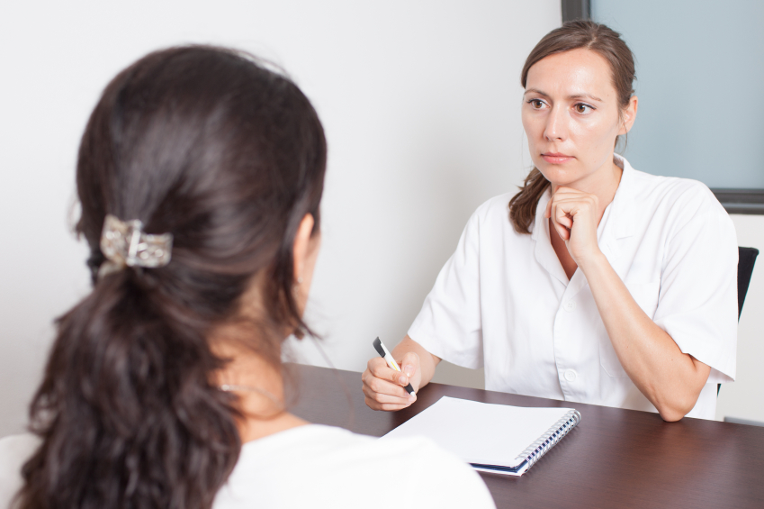 female doctor writing notes while talking to a patient
