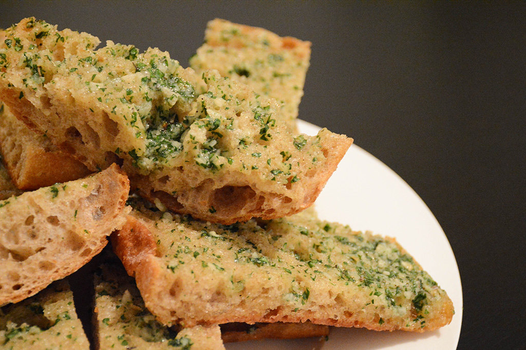 close-up image of a plate of garlic bread with lots of herbs