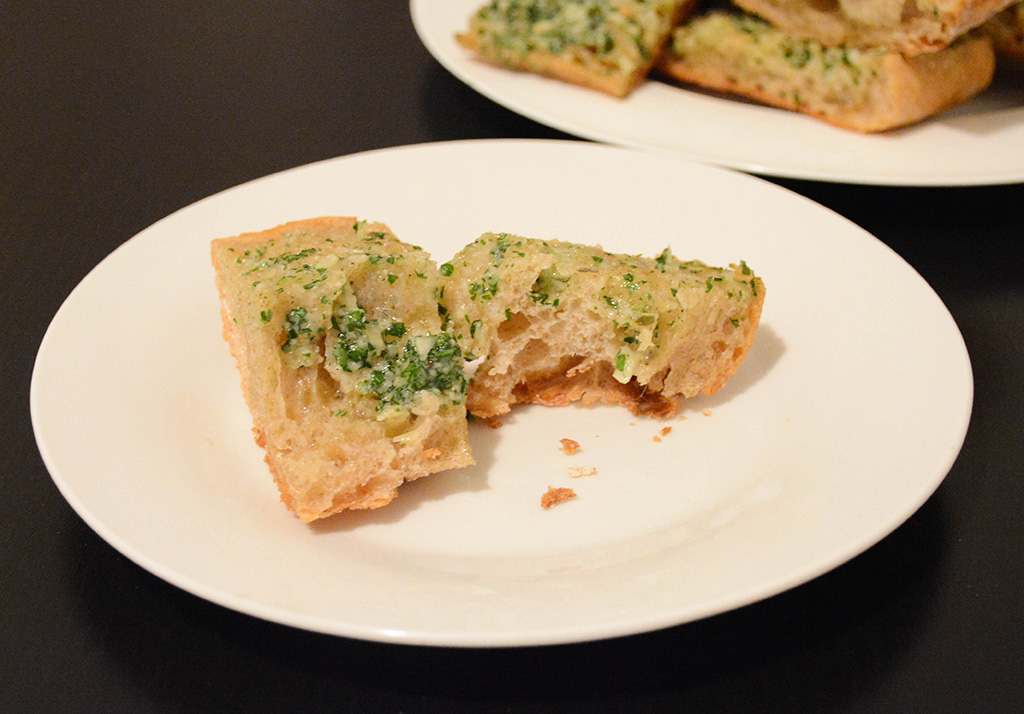 piece of buttery garlic bread with herbs on a plate that's been bitten