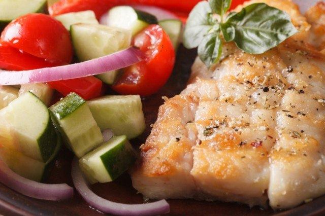 grilled fish with zucchini, onions, tomatoes, and herbs
