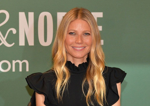 Gwyneth Paltrow in a black dress, smiling for the camera on the red carpet.