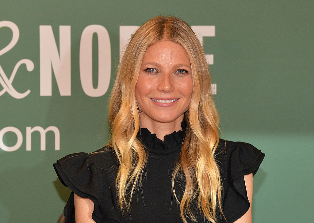 Gwyneth Paltrow in a black dress, smiling for the camera on the red carpet