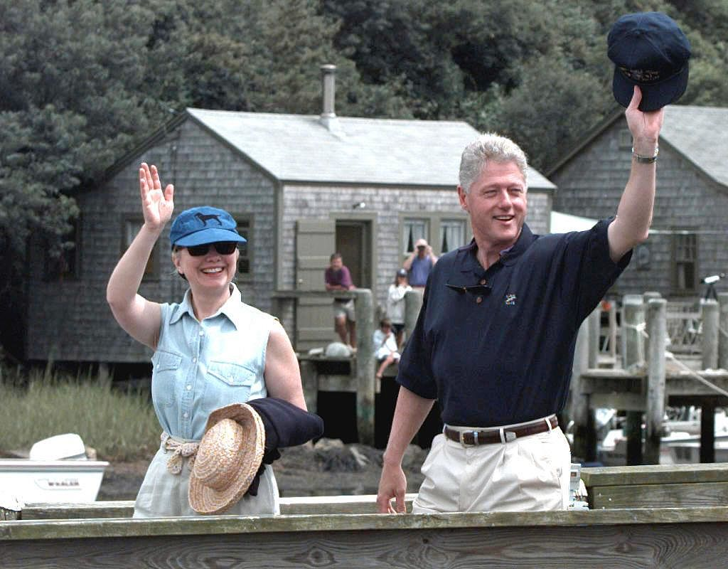 Hillary and Bill Clinton are walking on a dock and waving to people.