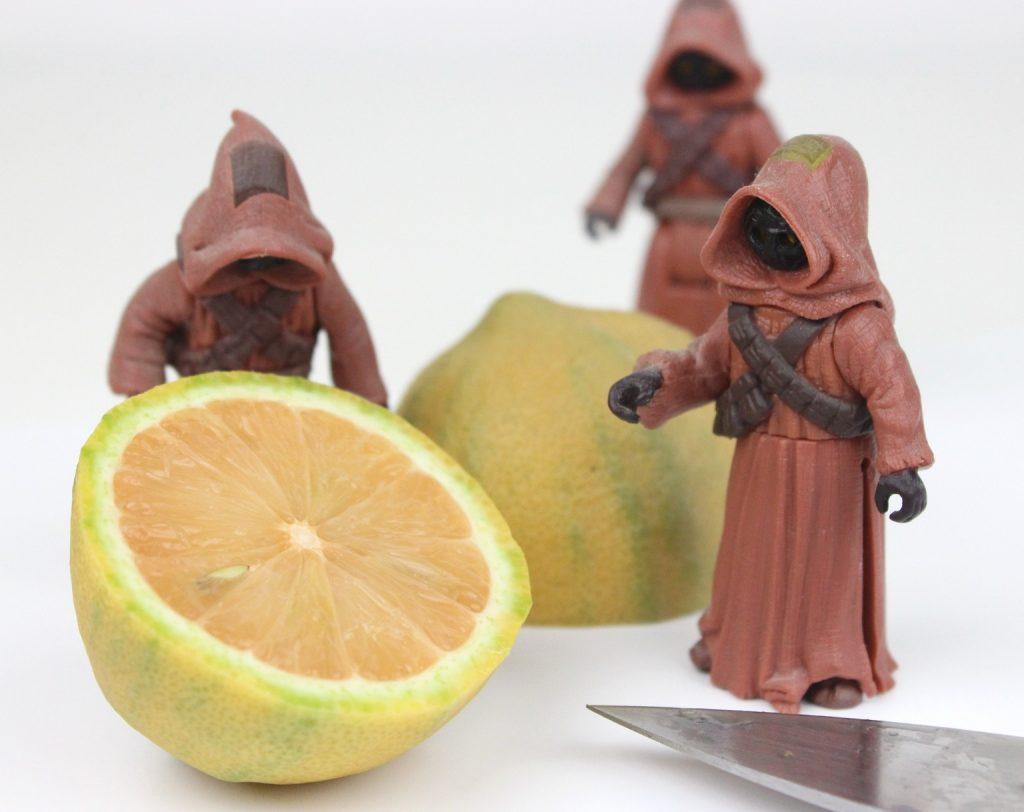 Jawa action figures stand amongst a cut lemon