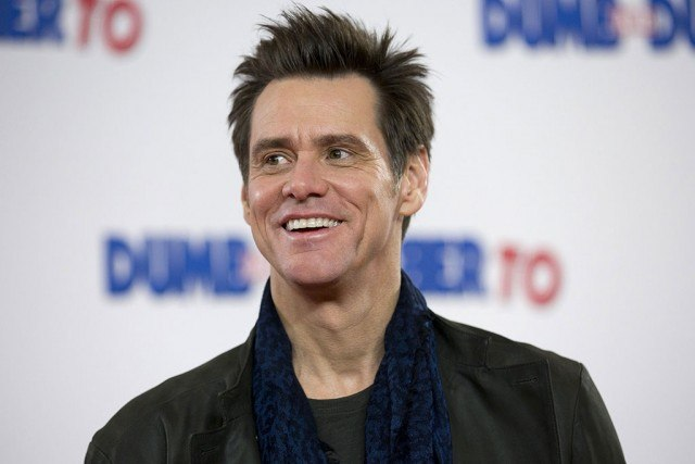 Jim Carrey smiles and poses for photographers in London.