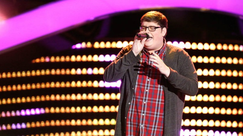 Jordan Smith has his eyes closed and is singing into a microphone on The Voice.