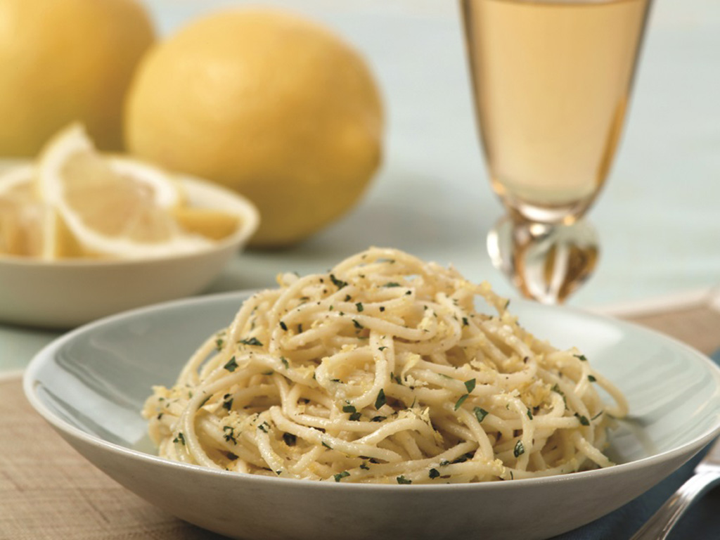 white bowl filled with spaghetti with lemon and basil