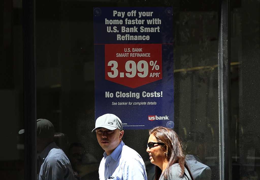 Pedestrians pass by a sign advertising low refinance rates at a US Bank office