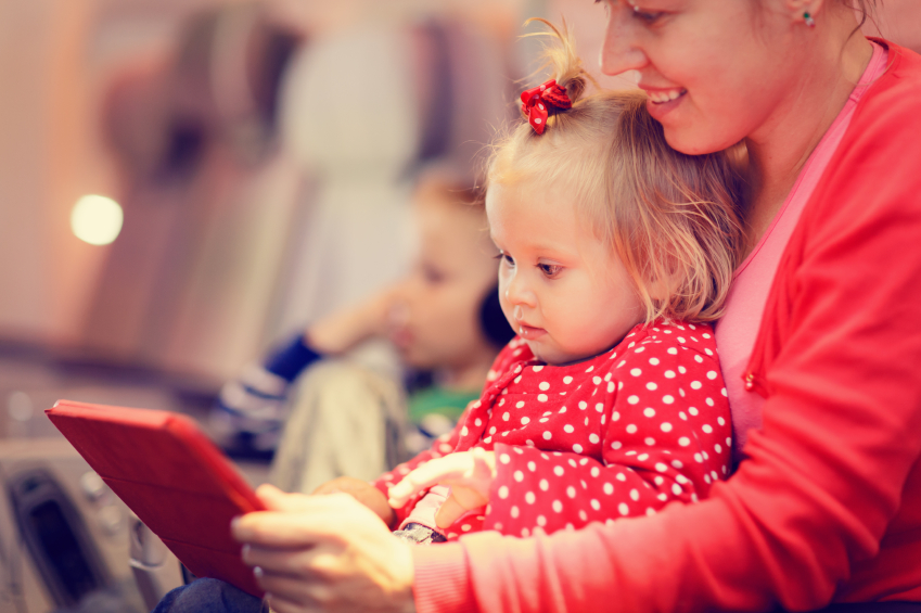 mother and little daughter looking at touch pad in plane