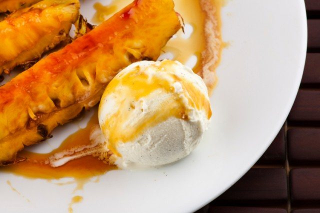 close-up of a portion of caramelized pineapple served with ice cream and syrup