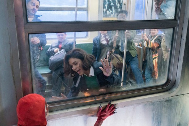 Vanessa Hudgens looks at a superhero out of the window of a subway car in Powerless
