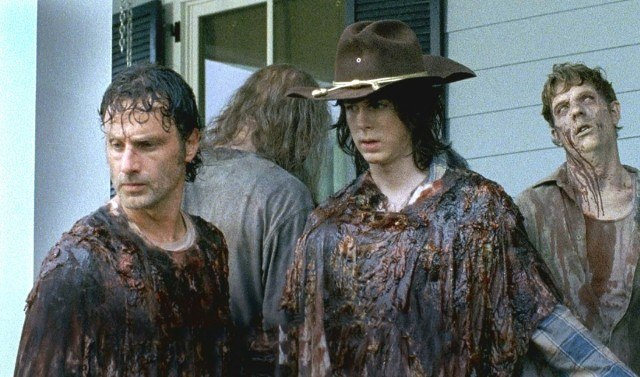 """Rick (Andrew Lincoln) and Carl (Chandler Riggs) wear guts as a means to protect themselves from the walkers invading Alexandria in a scene from 'The Walking Dead's sixth season episode """"No Way Out"""""""
