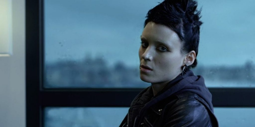 Rooney Mara, with a black mohawk, piercings, and wearing all black