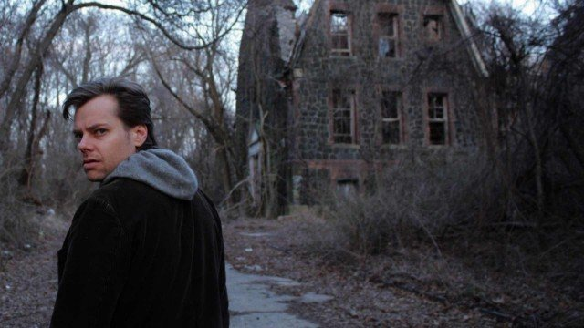 Joshua Zeman stands in front of a decrepit building in a scene from the documentary 'Cropsey', documentaries