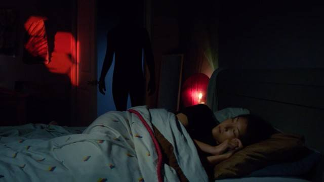 An ominous creature stands over the bed of a young woman in a scene from the sleep paralysis documentary 'The Nightmare' documentaries