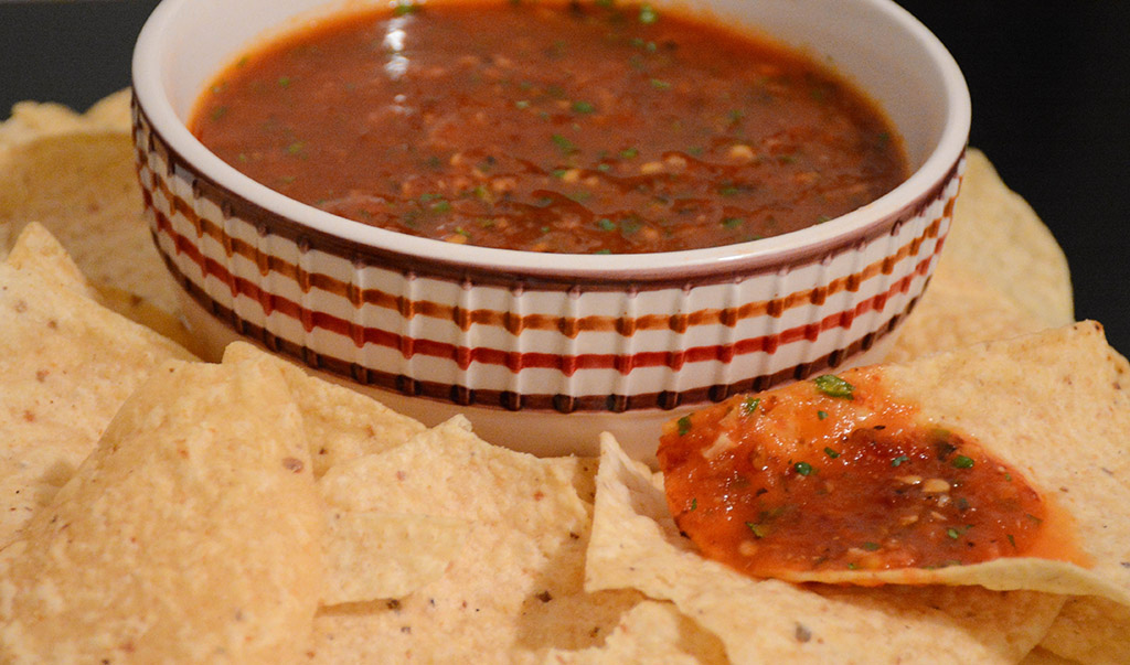 close-up of a tortilla chip dipped into smoky tomato salsa