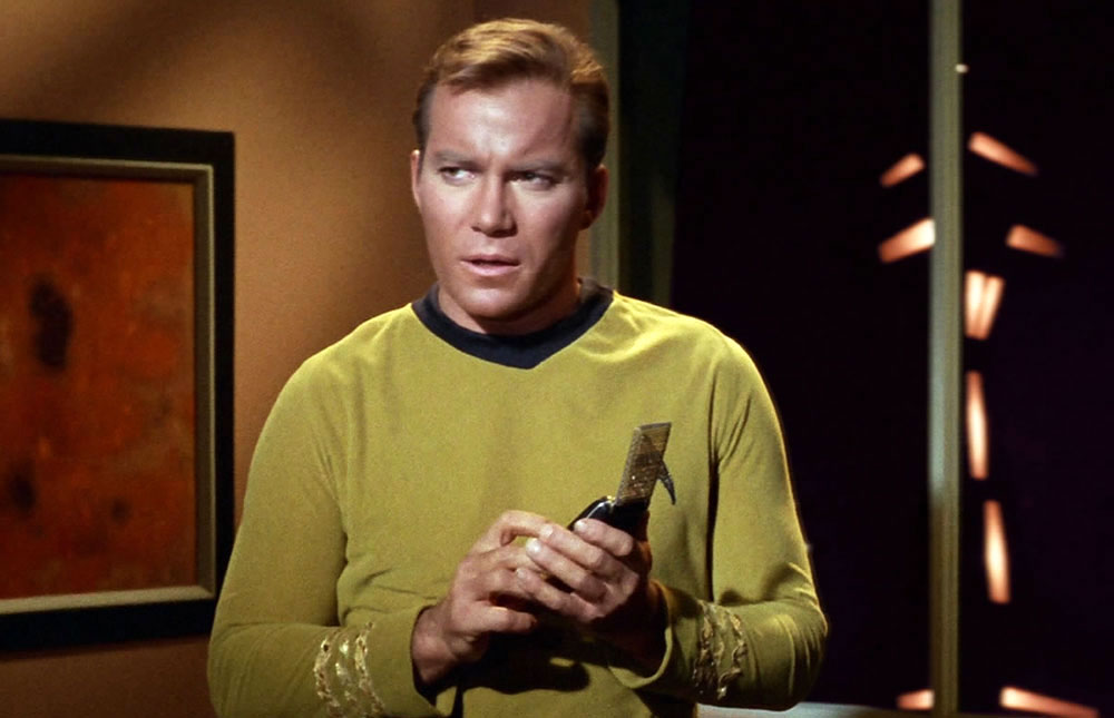 Captain Kirk looking concerned, holding a communicator with both hands