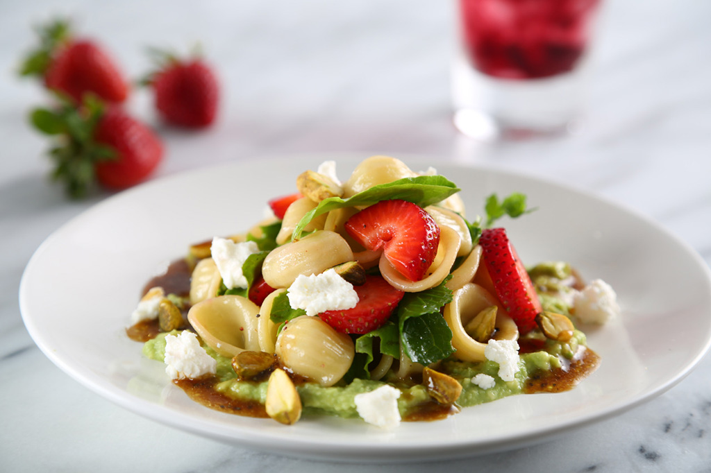 strawberry and orechiette pasta salad on a white plate