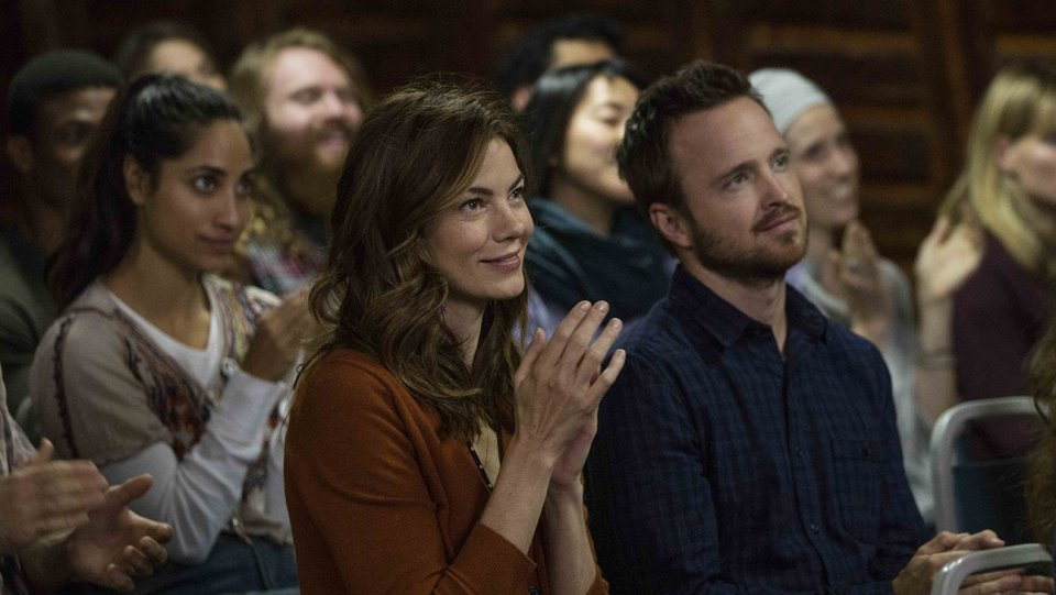 Michelle Monaghan claps while sitting next to Aaron Paul in a scene from The Path
