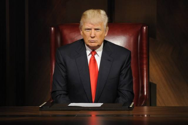 Donald Trump sits behind his desk in a scene from the reality TV series 'The Apprentice.'