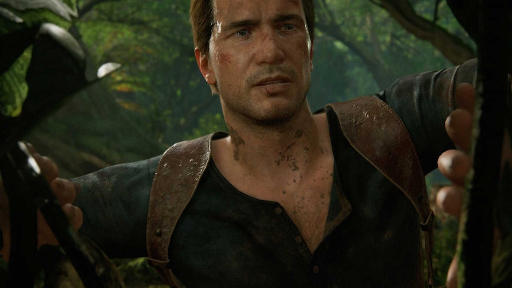 Uncharted's Nathan Drake peeks through foliage in a jungle.