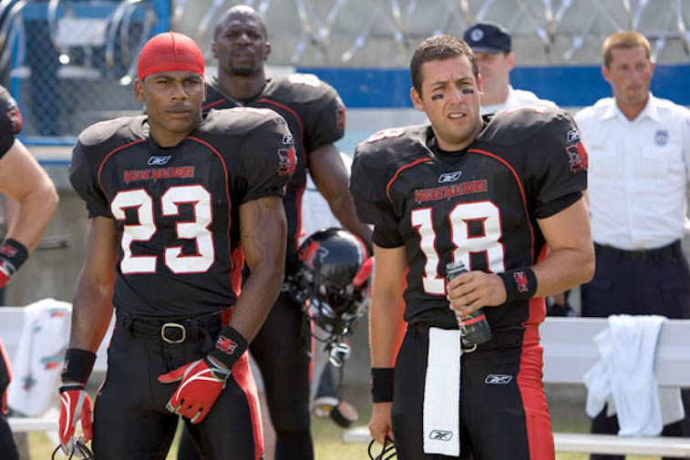 Adam Sandler stands next to other football players on the field in 'The Longest Yard'