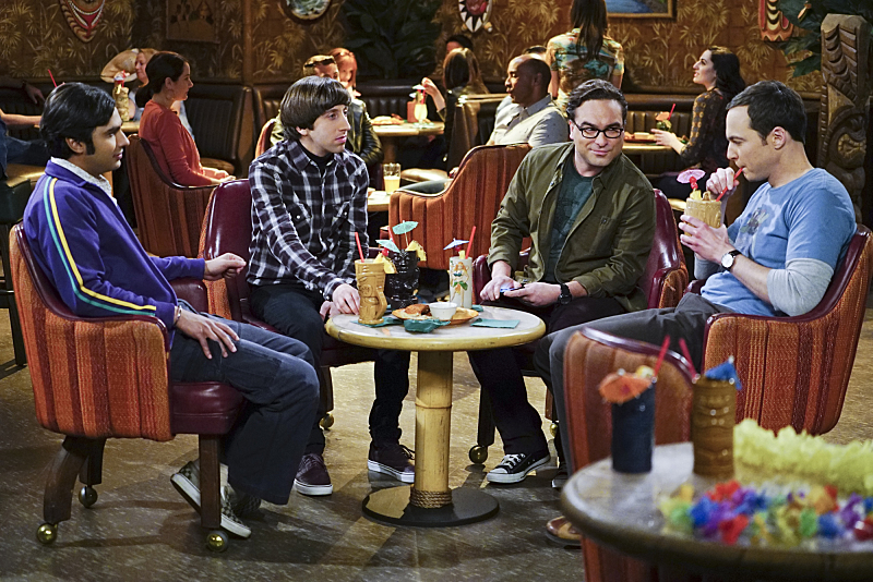 The cast of CBS's Big Bang Theory sit around a table with drinks
