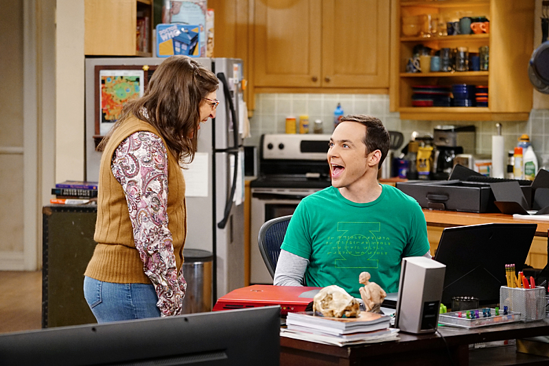 Sheldon laughs while sitting at his desk and looking at Amy