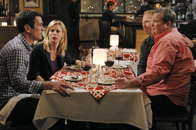 Julie Bowen, Ty Burrell, Jesse Tyler Ferguson and Eric Stonestreet sit at a restaurant table in Modern Family