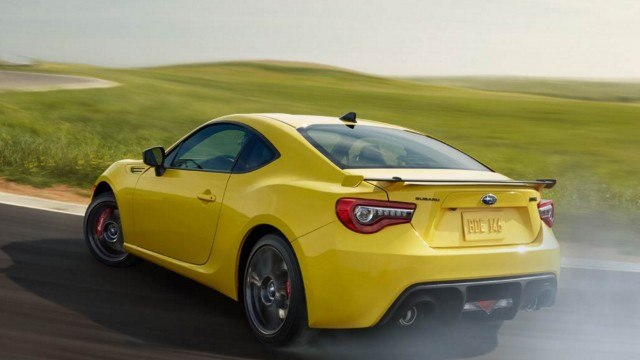 A Subaru BRZ in yellow accelerates aggressively, smoking the rear tires