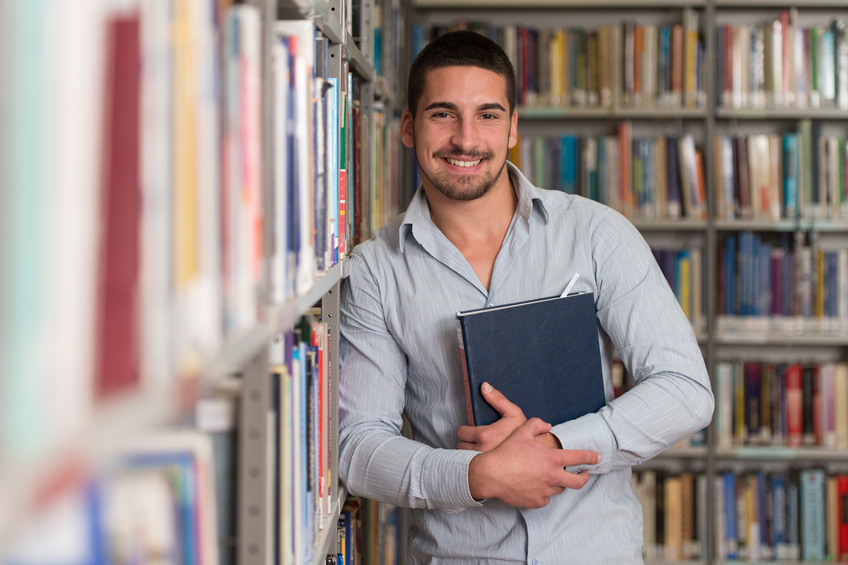 Smiling student holding a book in library
