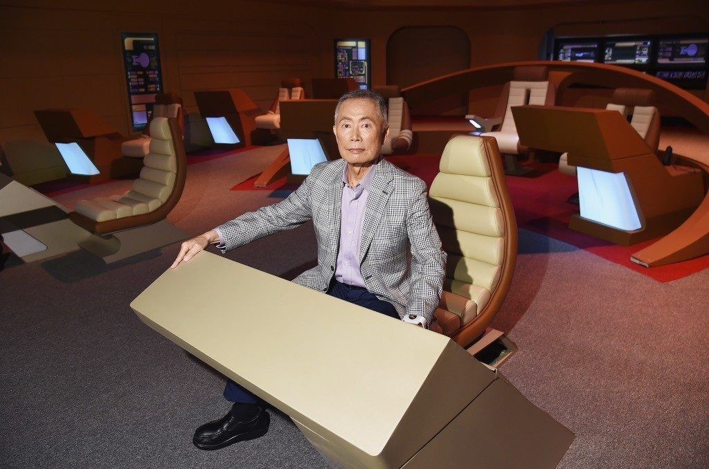 Actor George Takei at a desk on the set of Star Trek