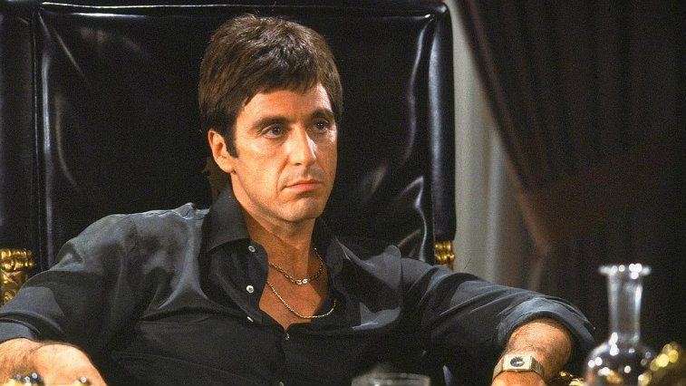 Al Pacino in Scarface sitting in a large leather chair.