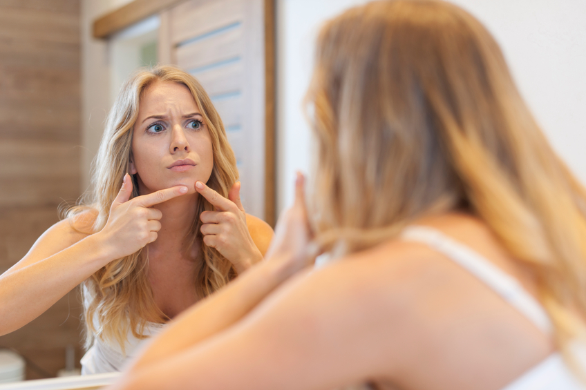 woman squeezing pimple in front of mirror