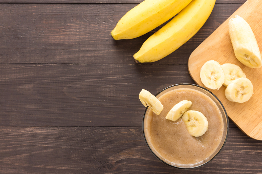Banana smoothie on wooden background