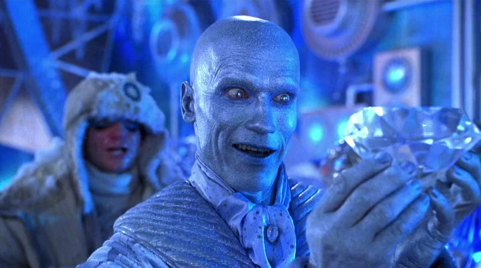 Mr. Freeze, with blue skin and a blue suit, smiling intently as he looks at a large diamond held in his hands