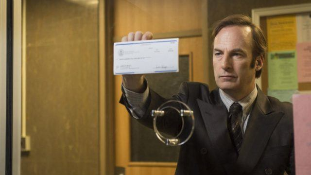 Saul holds up a check against a glass window.
