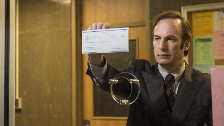 Bob Odenkirk holds up a check in AMC's Better Call Saul