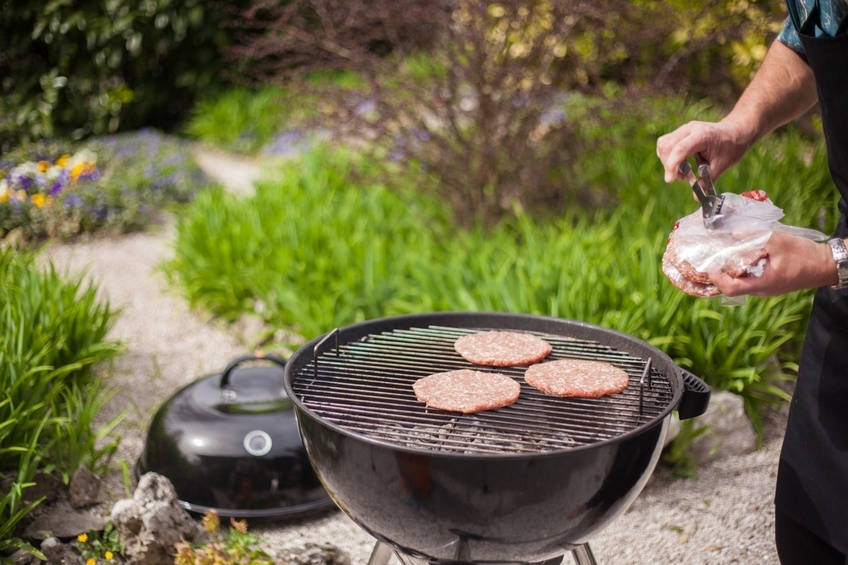 man preparing burgers on a charcoal grill