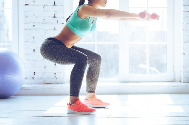woman doing squats with dumbells in hands