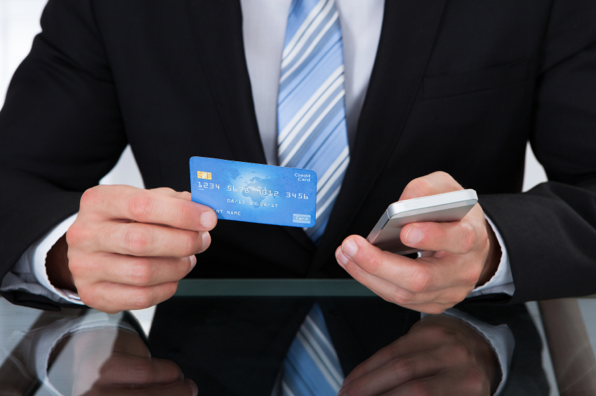 Businessman holding credit card and cell phone
