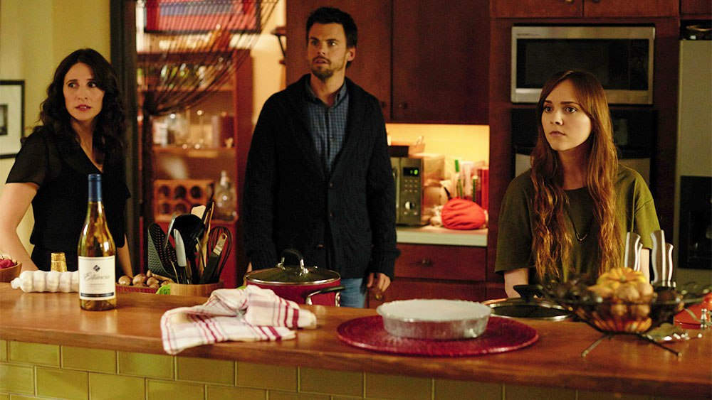 Two adults and a young woman stand behind a counter in a kitchen in Casual