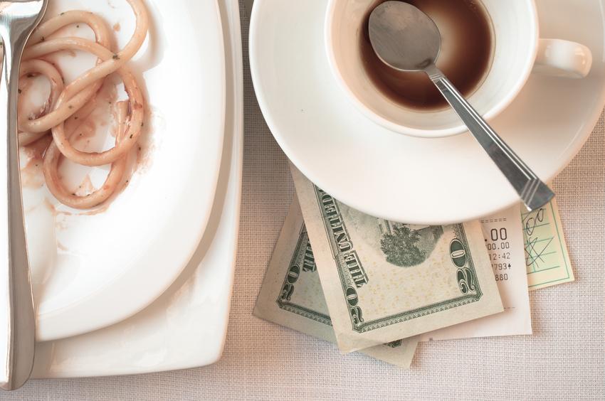 dollar bills under empty tea cup