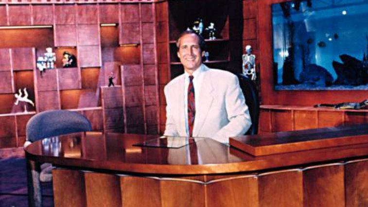Host Chevy Chase at his desk on The Chevy Chase Show