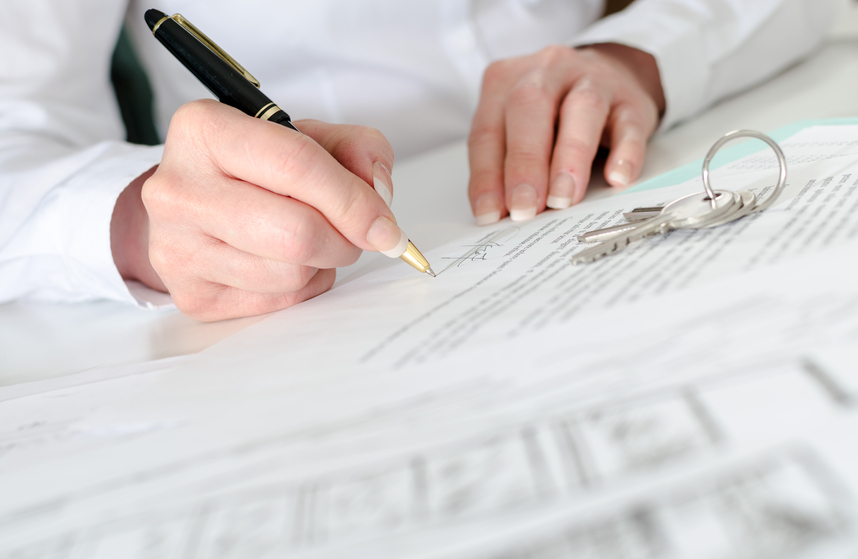 A woman signs a mortgage document