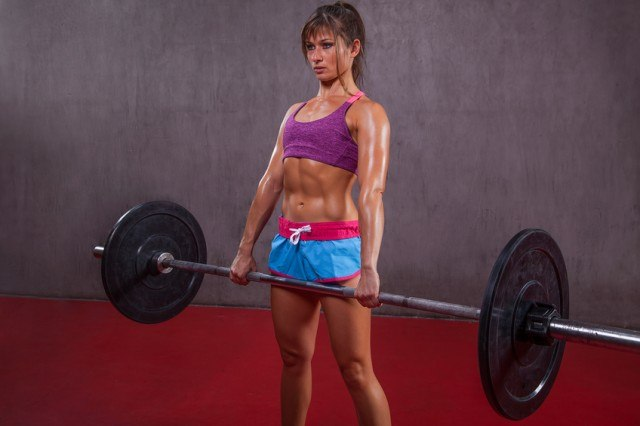 girl performing a barbell deadlift
