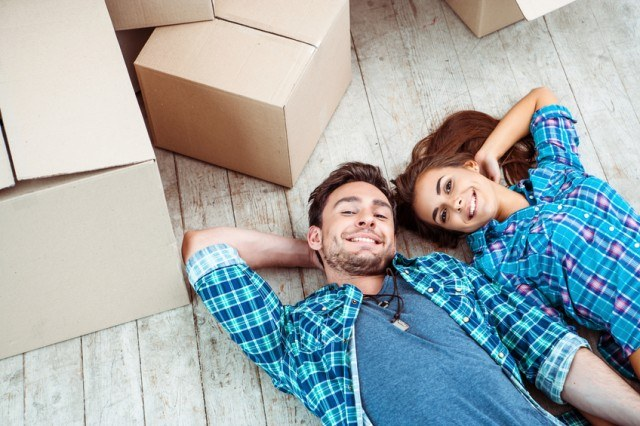 Happy couple lying on floor with cartons